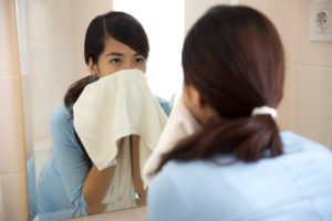 woman wiping her oily skin with a towel after washing face considering Wheaton oily skin treatment