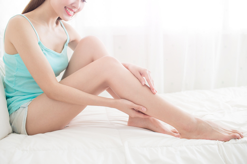 woman touching smooth legs after Wheaton laser hair removal treatment